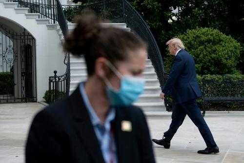 محافظ ماسک زده ترامپ (سرویس مخفی) در محوطه کاخ سفید. کاخ سفید هفته گذشته زدن ماسک در مقر قوه اجراییه آمریکا را الزامی کرد. ترامپ خود هنوز عامدانه از زدن ماسک در مقابل دوربین خبرنگاران خودداری میکند. / خبرگزاری فرانسه
