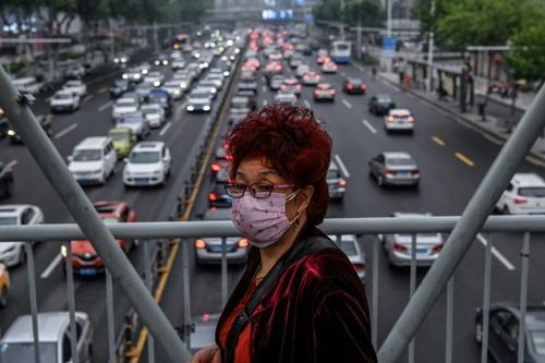 عبور از پل عابر پیاده در شهر ووهان چین/ خبرگزاری فرانسه