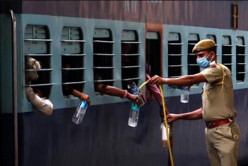پلیس هند در حال پر کردن بطریهای آب کارگران مهاجر هندی عازم شهرهایشان در ایستگاه راه آهن/ خبرگزاری فرانسه