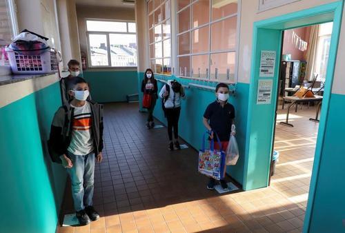 دانشآموزان با رعایت پروتکلهای بهداشتی و فاصلهگذاری در انتظار ورود به کلاسهای درس در دبستانی در شهر