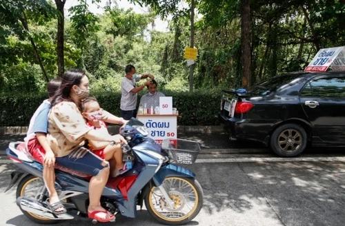 صاحب یک مغازه جواهرات در شهر بانکوک تایلند که کسب و کارش به دلیل بحران کرونا هنوز تعطیل است، به دلیل داشتن مهارت آرایشگری، یک آرایشگاه کنار خیابانی دایر کرده است./ EPA