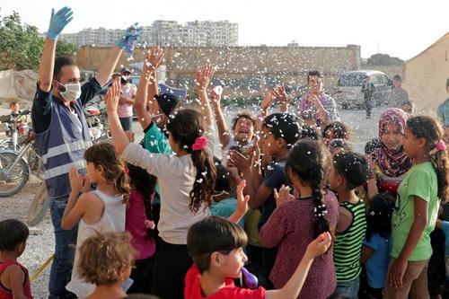 یک نیروی داوطلب انجمن بینالمللی امداد و توسعه (ONSUR) پیش از تعطیلات عید فطر در حال سرگرم کردن کودکان در اردوگاه آوارگان در استان ادلب سوریه /رویترز