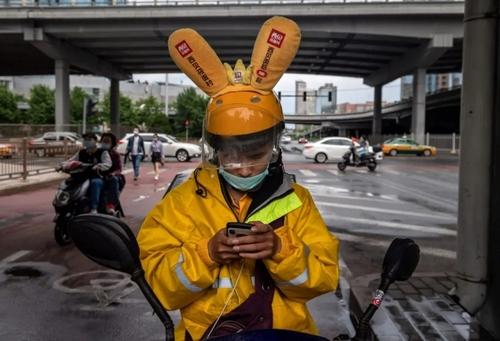 پیک موتوری در شهر پکن چین در حال نگاه کردن به نقشه مسیر از گوشی تلفن همراه/ خبرگزاری فرانسه