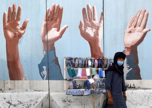 نوجوان ماسک فروش افغان در شهر کابل/ رویترز