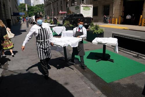چیدن میزهای یک رستوران در پیادهرو یک خیابان در محله منهتن نیویورک در پی بازگشایی مشاغل / رویترز