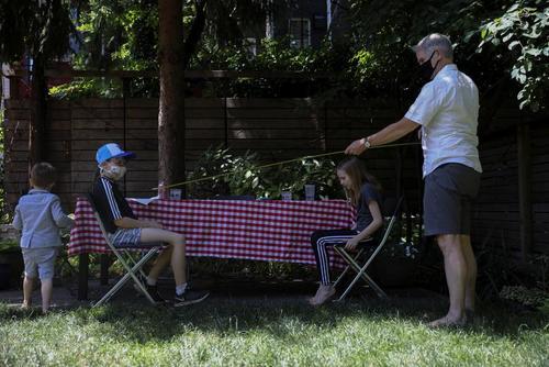 تنظیم فاصله اجتماعی از سوی پدر برای همنشینی فرزند با دوستش در حیاط خانه/ محله بروکلین نیویورک/ رویترز
