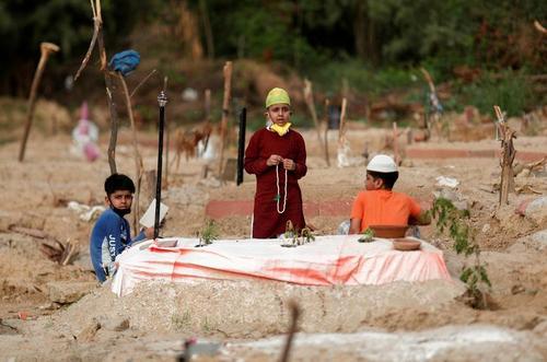 نوجوان هندی مسلمان در حال قرائت قرآن بر سر مزار یک فوتی کرونایی در شهر دهلی/ رویترز