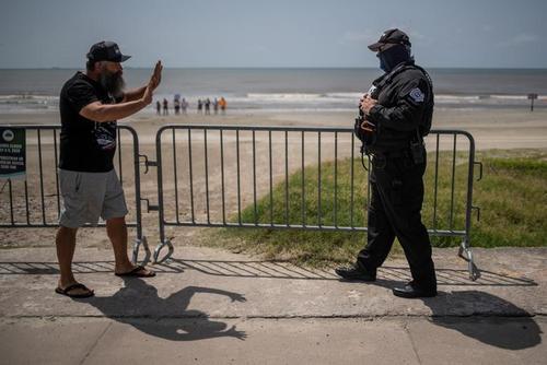 یک شهروند آمریکایی در تگزاس که به بسته بودن سواحل اعتراض دارد از پلیس میخواهد فاصله اجتماعی با او را حفظ کند/ رویترز