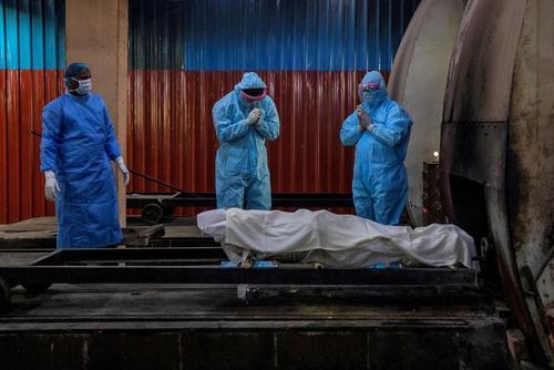 دعا برای یک زن هندو فوت شده در اثر کرونا پیش از فرستادن جسدش به داخل کوره/دهلی نو/ رویترز