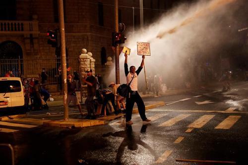 تظاهرات شبانه معترضان در نزدیکی اقامتگاه نتانیاهو در شهر قدس در اعتراض به سوء مدیریت دولت در بحران کرونا. پلیس برای متفرق کردن معترضان به ماشین آبپاش متوسل شد. / رویترز