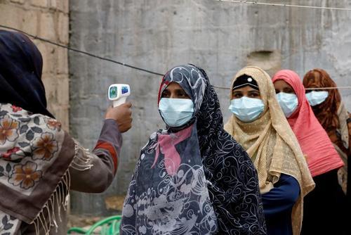 کنترل دمای بدن اعضای کادر بهداشتی تیم واکسیناسیون فلج اطفال پیش از اعزام آنها به ماموریت در شهر کراچی پاکستان/ رویترز
