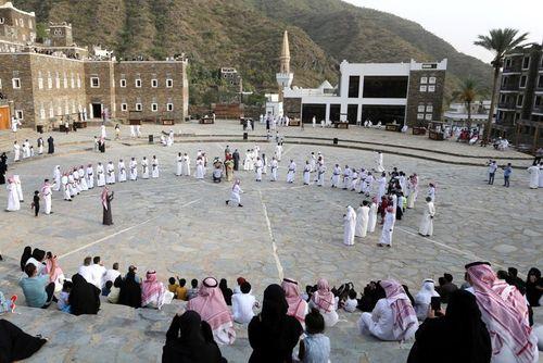 گردشگران داخلی سعودی در حال تماشای رقص سنتی در روستای گردشگری