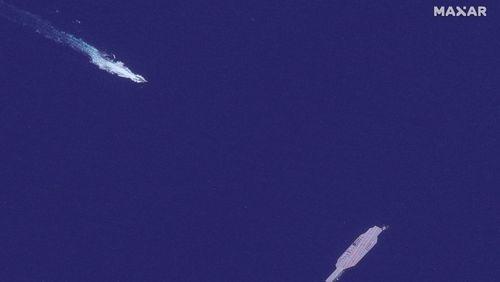 تصویر  کشیدن ماکت ناو به سمت تنگه هرمز با استفاده از قایق های تندرو و کشتی