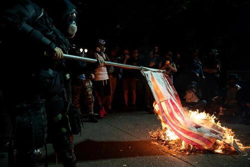 به آتش کشیدن پرچم ایالات متحده آمریکا در جریان تظاهرات ضدنژادپرستی در شهر پورتلند ایالت اورگان آمریکا/ رویترز