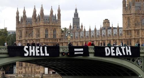 اعتراض به تاثیر فعالیت های شرکت های بزرگ علیه محیط زیست . معترضان پارچه نوشته بزرگی را با این متن در یکی از پل های رود تیمز لندن نصب کرده اند: شل (شرکت نفتی)= مرگ
