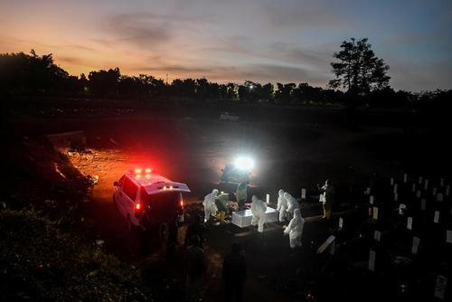 کارگران با لباسهای محافظتی یکی از قربانیان ویروس کرونا را در قبرستان