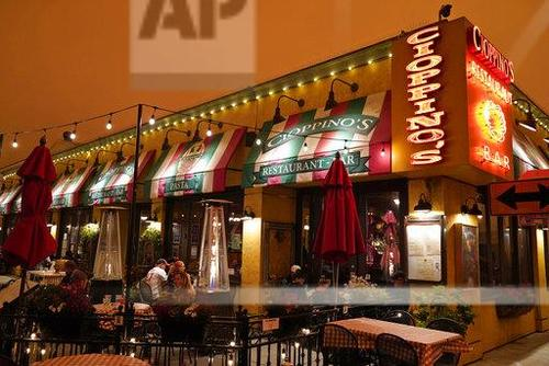 در زیر آسمان نارنجی و پردود ناشی از آتشسوزی گسترده در کالیفرنیا، عدهای در یکی از رستوران سنفرانسیسکو در حال صرف ناهار هستند/ اسوشیتدپرس