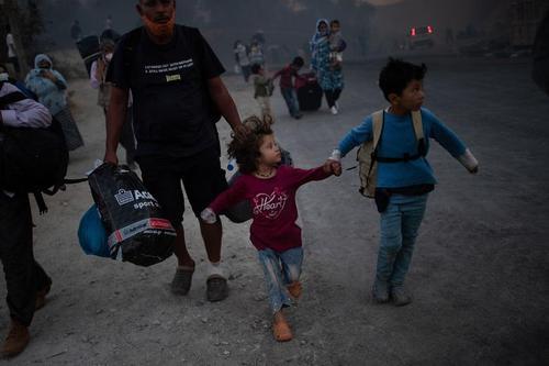 دو کودک در حال فرار از اردوگاه در حال سوختن پناهندگان و مهاجران
