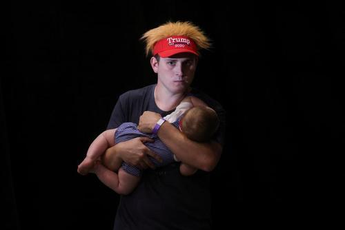یکی از طرفداران ترامپ در حال آرام کردن فرزندش در پشت سالن اصلی کمپین انتخاباتی