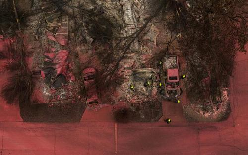 تیم امداد و نجات در حال بررسی منطقه سوخته. آنها در میان خودروها و محوطه سوخته به دنبال قربانیان آتشسوزی منطقه