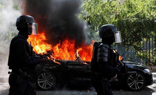 دو افسر پلیس ضد شورش پس از تظاهرات جلیقه زردها از کنار یک خودروی در حال سوختن در پاریس میگذرند/ رویترز