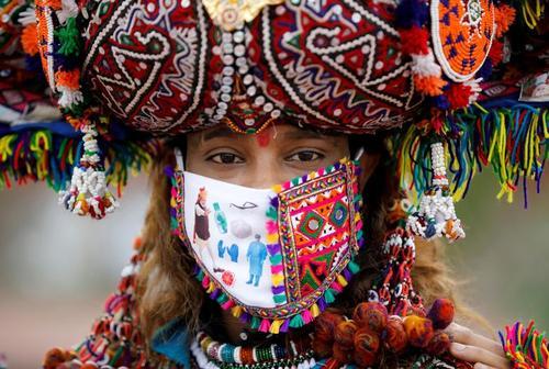یک شرکت کننده با لباس محلی و ماسک در تمرین یک رقص محلی در یکی از مراسمهای آئینی هندو در