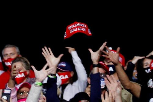 تلاش حامیان ترامپ برای گرفتن کلاه او در جریان یک گردهمایی تبلیغاتی- انتخاباتی ترامپ در شهر