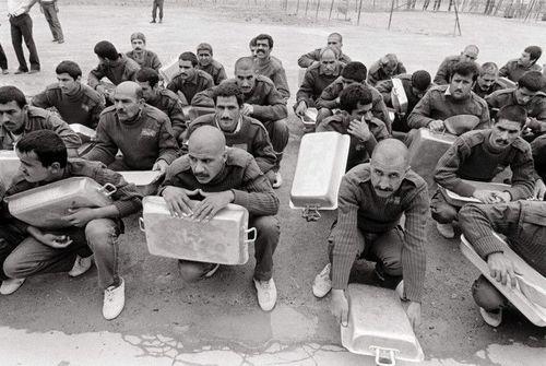 2 آوریل 1985 - اسرای جنگی ایرانی در اردوگاه رمادی عراق در انتظار دریافت غذای روزانه نشسته اند.
