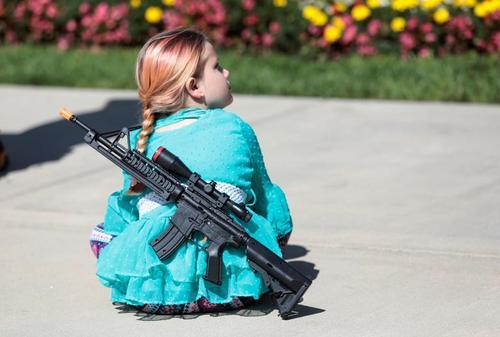 یک دختر بچه با تفنگ اسباب بازی در حاشیه راهپیمایی حامیان حمل آزاد اسلحه در میشیگان آمریکا/ رویترز