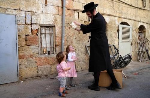 یک مرد یهودی ارتدوکس در شهر قدس (اورشلیم) در حال چرخاندن یک مرغ بالای سر فرزندانش برای آمرزش گناهان یک ساله و انداختن مسئولیت گناهان یک ساله به مرغ/ خبرگزاری فرانسه