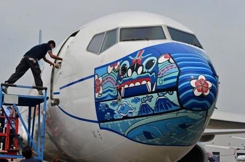 کشیدن ماسک روی بدنه هواپیمای مسافربری/ اندونزی/ خبرگزاری فرانسه