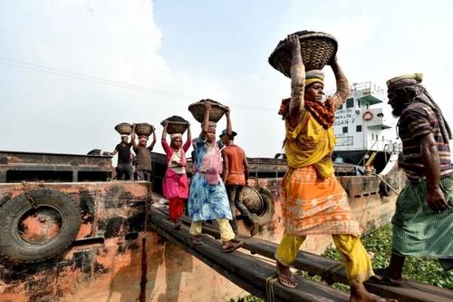 کارگران در حال خالی کردن محموله ذغال سنگ از داخل کشتی/ شهر داکا بنگلادش/ شینهوا