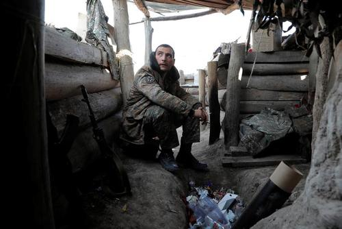 یک سرباز ارتش ارمنستان در حال کشیدن سیگار درون سنگری در منطقه قره باغ/ رویترز