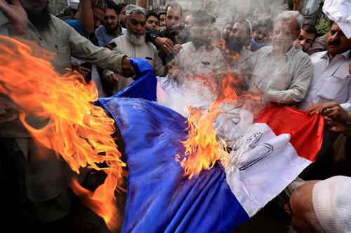 معترضان در شهر پیشاور پاکستان در حال آتش زدن پرچم فرانسه/ رویترز