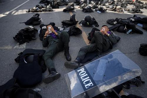 پلیس تایلند در حال گوشی بازی در تظاهرات دموکراسیخواهان تایلندی در شهر بانکوک/ رویترز