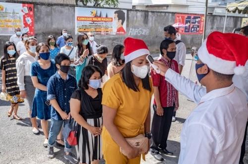 کنترل دمای بدن شرکت کنندگان در مراسم کریسمس کلیسایی در جزیره بالی اندونزی/ EPA