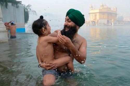 آبتنی پدر و فرزند سیک هندی در مقابل معبد طلایی به مناسبت سال نو میلادی/ آمریتسار هند/ خبرگزاری فرانسه