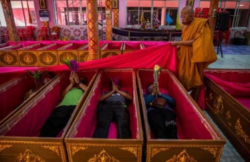 زائران تایلندی در یک معبد در سال نو در تابوتها دراز میکشند به امید پاک کردن کردار بد از خود  و تولد دوباره/ گتی ایمجز