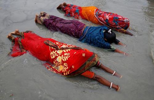 زنان هندو در جریان یک جشنواره آیینی در کرانه رود گنگ به نیایش خدای آفتاب می پردازند./ رویترز