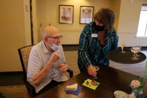 پذیرایی با نوشیدنی شامپاین از پیرمرد 89 ساله آمریکایی پس از زدن واکسن کرونا در یک خانه سالمندان در