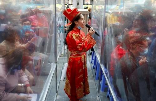 یک کارمند فروشگاه جواهرات سازی در شهر هانوی ویتنام که لباس خدای ثروت را پوشیده مردم را تشویق به خرید طلا می کند./ رویترز