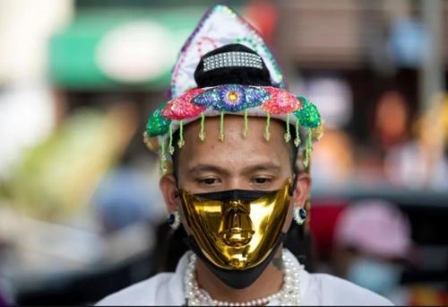 زدن ماسک طلایی از سوی یکی از معترضان به کودتای ارتش میانمار در جریان تظاهراتی در شهر یانگون/ رویترز