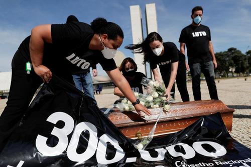 کارمندان کادر بهداشت و درمان برزیل در اعتراض به نحوه مدیریت بحران ویروس کرونا به صورت نمادین روی تابوت گل گذاشته و به مرگ همکاران خود اعتراض دارند/ عکس: رویترز