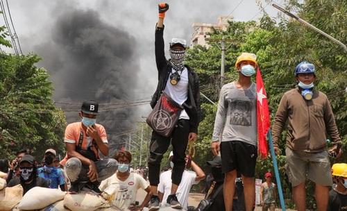 گروهی از معترضان به کودتا در کنار موانع ساخته شده برای تظاهرات در شهر یانگون میانمار ایستادهاند/  عکس: رویترز