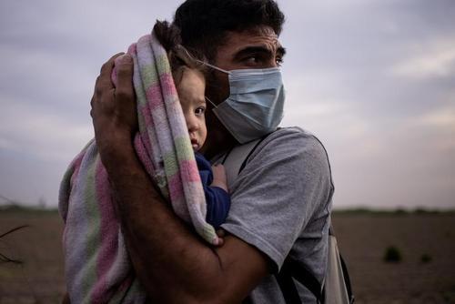 یک مهاجر هندرواسی در مزرهای مکزیک و آمریکا دختر 9 ماهه اش را در برابر باد سرد می پوشاند/ عکس: رویترز