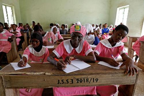 زن 50 ساله نیجریه ای در مدرسه و با دانش آموزان 40 سال پایین تر از خود درس می خواند./ رویترز