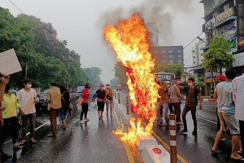 آتش زدن پرچم چین از سوی معترضان به کودتای نظامی در میانمار. دولت چین از موضع دولت نظامی میانمار حمایت می کند./ رویترز