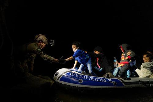 کمک نیروهای گارد مرزی آمریکا به پناهجویان آمریکای مرکزی برای پیاده شدن از قایق در رود