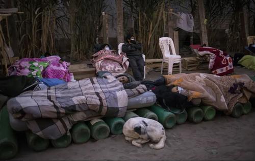 خوابیدن روی کپسول های خالی اکسیژن در صف تعویض کپسول برای بیماران کرونایی در شهر