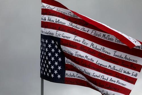 نوشتن نام کشته شدگان سیاه پوست در اثر تیراندازی پلیس آمریکا روی پرچم این کشور در جریان اعتراضات ضدنژادپرستی در شهر بروکلین در ایالت مینه سوتا/ رویترز